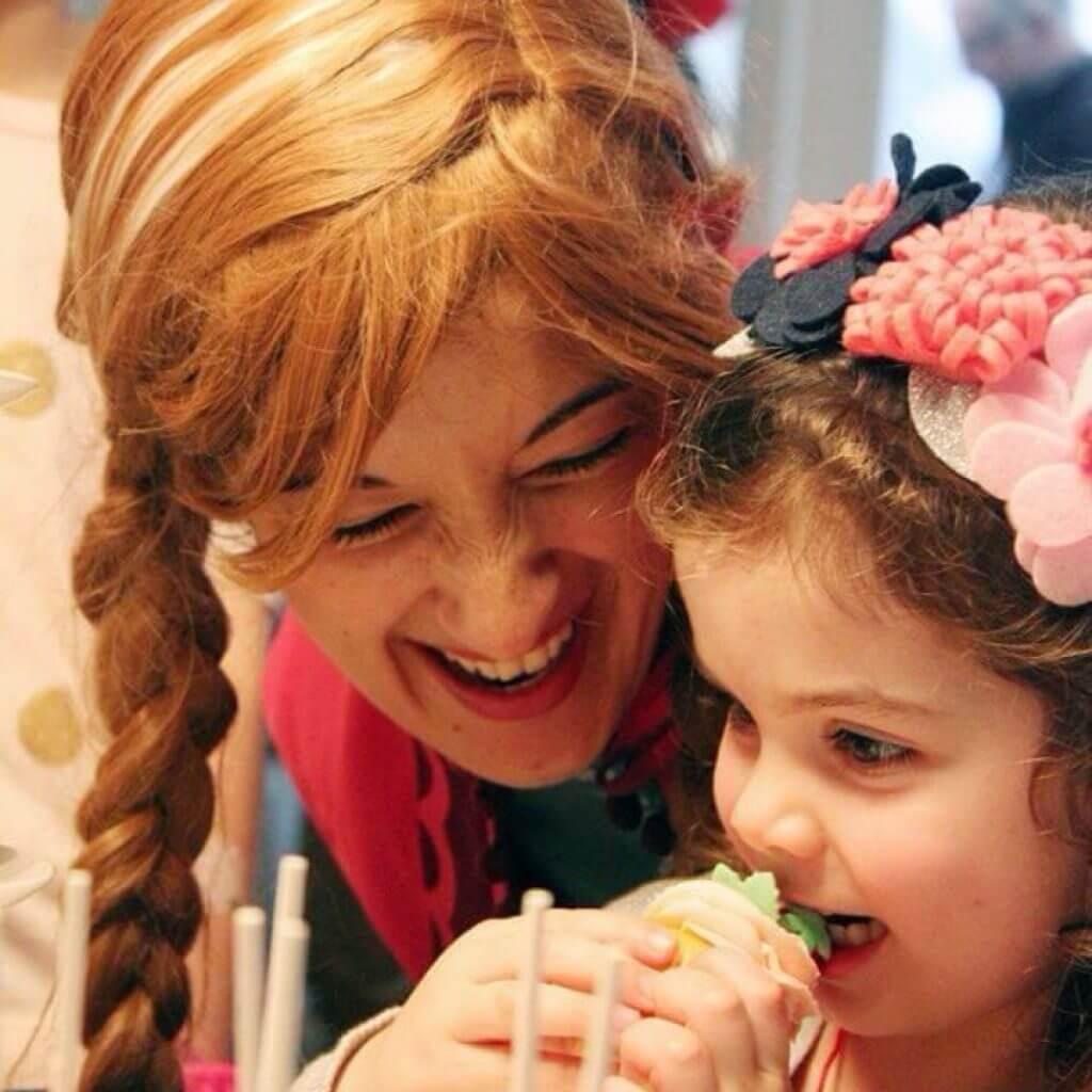 Anna feeding child cake
